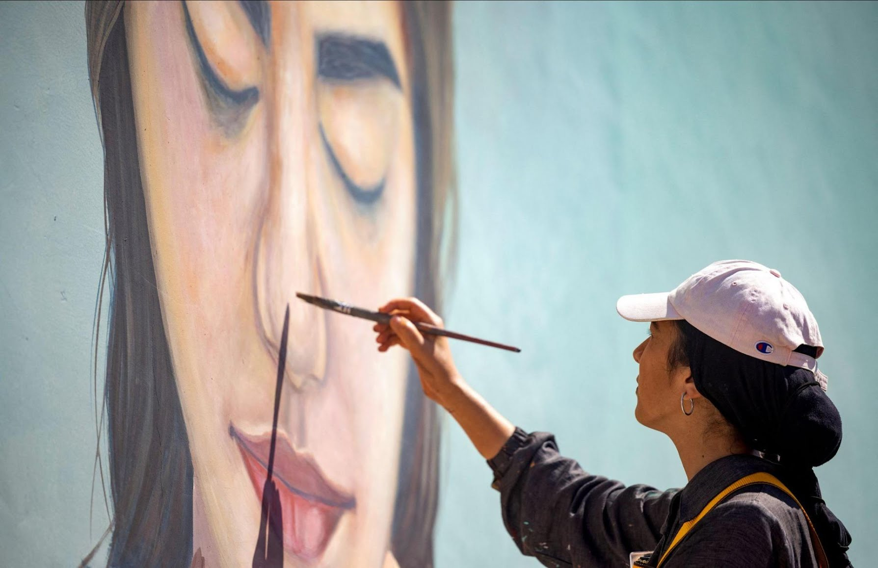 Moroccan street artist Imane Droby works on a mural during the 'Jidar' street art festival in the capital Rabat.